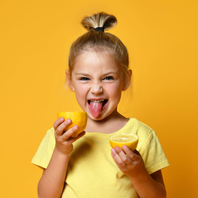 Little smiling cute blond girl in yellow t-shirt holding halves of fresh sour ripe lemon fruit and showing tongue over yellow background. Healthy lifestyle and clean eating concept
